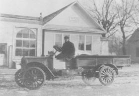 old photo of man driving car
